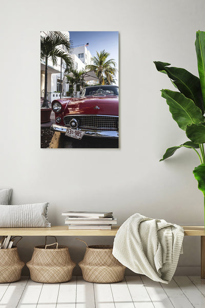 Vintage red Oldtimer car, parked in front of a hotel in Ocean Drive. Vertical photo shown on a white wall, in a modern interior.