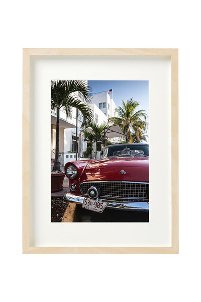 Vintage red Oldtimer car, parked in front of a hotel in Ocean Drive. Vertical photo shown in a boxed frame.