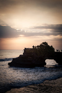 The sun sets over the Pura Batu Bolong beach, in Bali. As the waves crash in the sand, we see a small terrace built on rock formations and a bridge connecting it to the shore. People enjoy the sunset staring at the sun rays pierce the clouds in the sky.