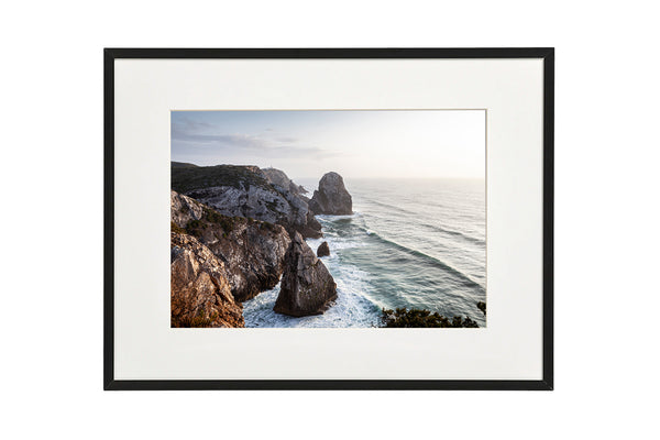Sunset at the Praia do Caneiro viewpoint overlooking the Atlantic Ocean. Horizontal photo shown in a normal frame.