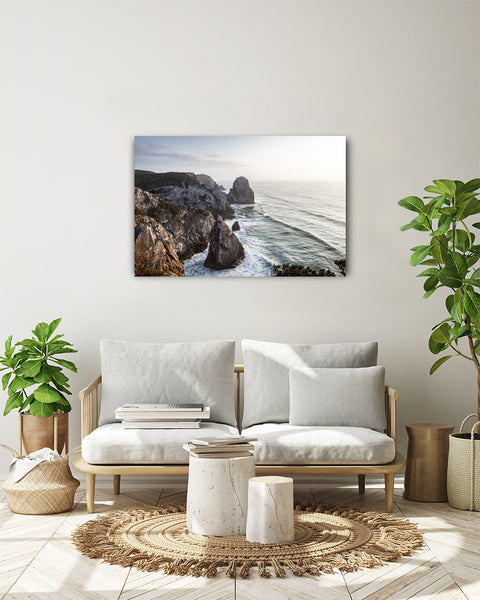 Sunset at the Praia do Caneiro viewpoint overlooking the Atlantic Ocean. Horizontal photo shown on a white wall, in a modern living room.