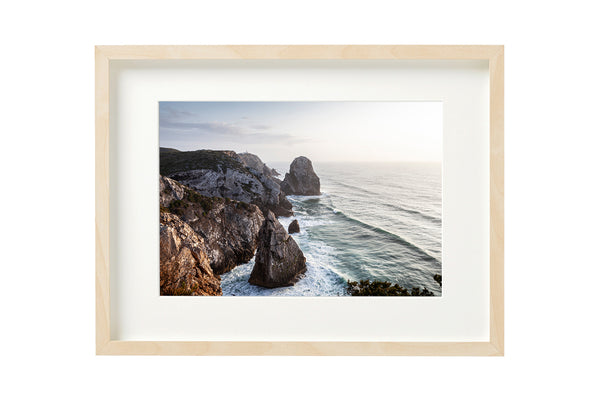 Sunset at the Praia do Caneiro viewpoint overlooking the Atlantic Ocean. Horizontal photo shown in a boxed frame.