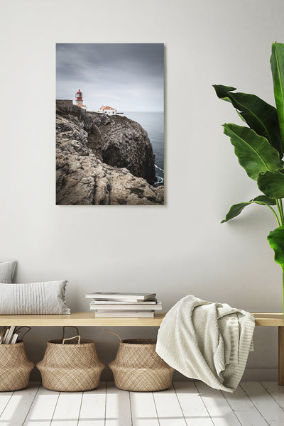 Vertical photo of the lighthouse in Cabo de São Vicente, shown on a white wall in a modern interior.