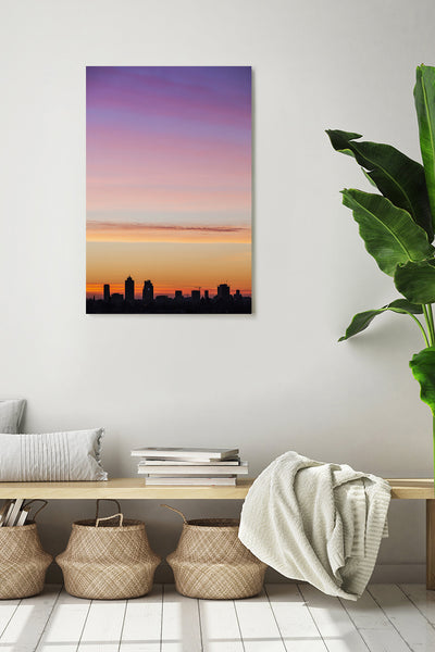 Sunrise behind the buildings of Amsterdam at the end of a winter day. Photo shown on a white wall in a modern interior.