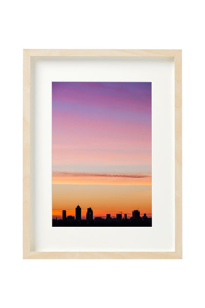 Sunrise behind the buildings of Amsterdam at the end of a winter day. Photo shown in a boxed frame.
