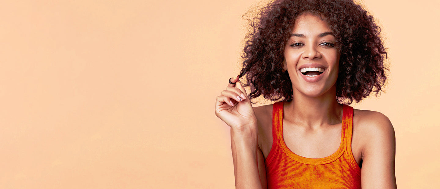 Girl in Orange Tank Twirling Hair and Smiling