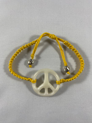 All natural Hand carved Peace Sign Tagua charm on a hand woven cotton bracelet by Tu y Yo
