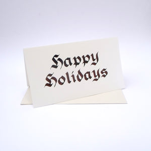 "Calligraphy Christmas card with ""happy holidays"" written in black red ink"