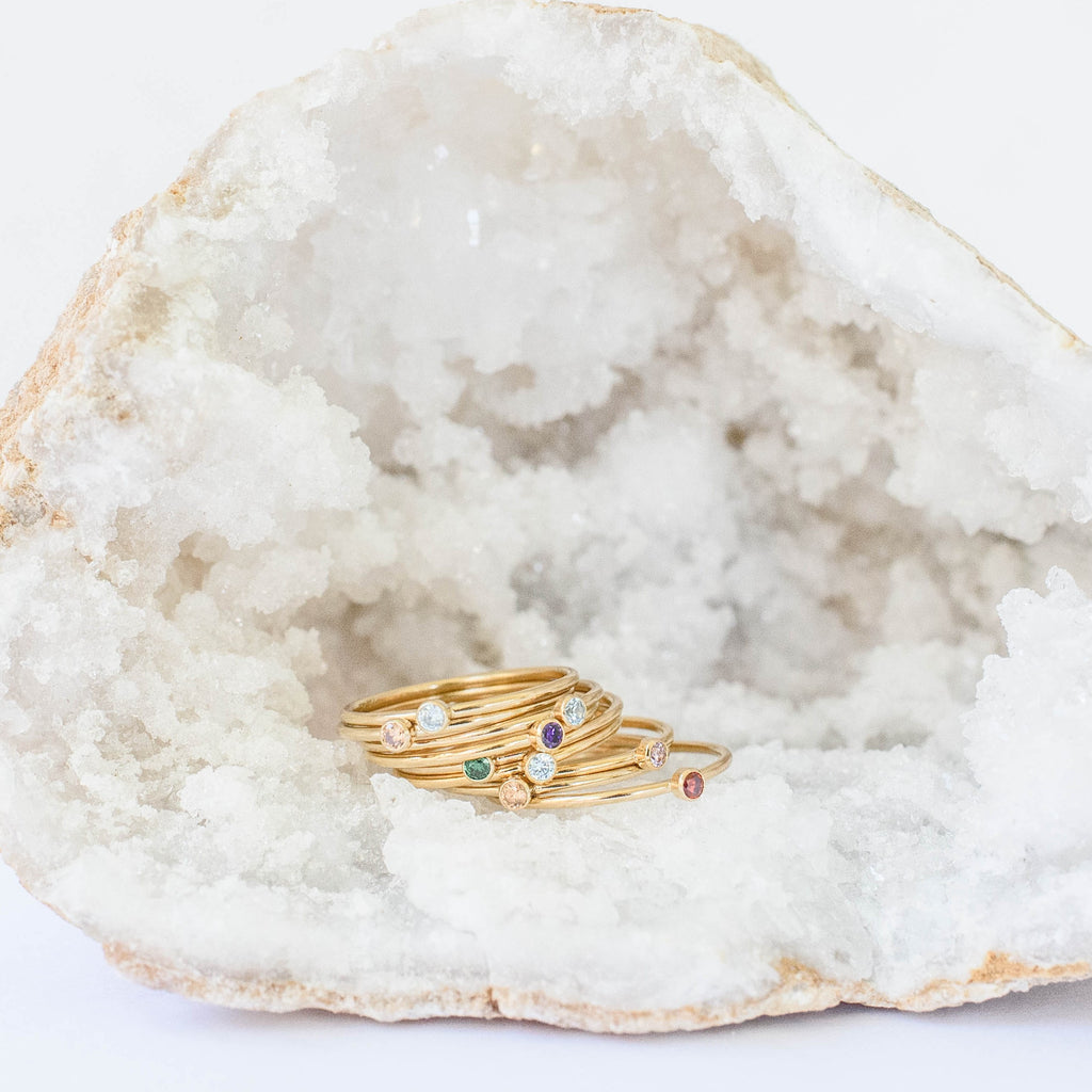 image of a crystal with a bunch of Yellow Gold Filled Stacking Birthstone Rings with colored cubic circonia bezel set stone