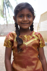 Female Indian child with a brown shirt rescued from slavery or human trafficking