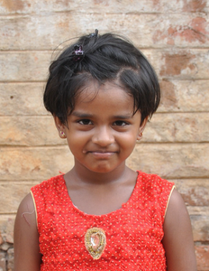 Little Indian girl with a red shirt rescued from slavery or human trafficking