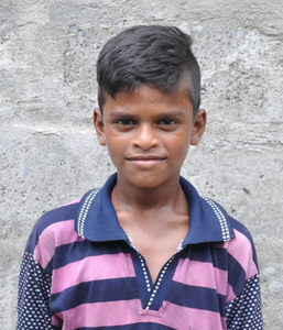 Male Indian child with a blue and pink polo rescued from slavery or human trafficking