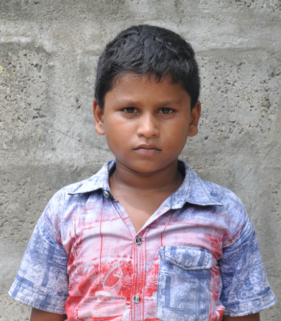 Little Indian boy with a blue and red shirt rescued from slavery or human trafficking