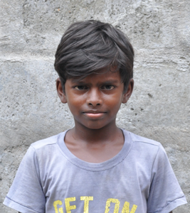 Little Indian boy with a grey shirt rescued from slavery or human trafficking