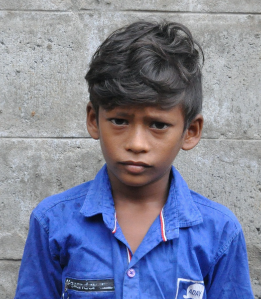 Little Indian boy with a blue shirt rescued from slavery or human trafficking