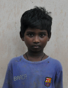 Male Indian child with a blue shirt rescued from slavery or human trafficking