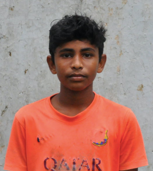 Young Indian male freed from human trafficking or slavery wearing orange and in need of scholarship support and sponsorship