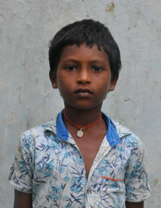 Male Indian child with a white shirt rescued from slavery or human trafficking