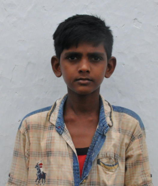 Male Indian child with a tan shirt rescued from slavery or human trafficking