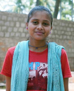 Little Indian girl rescued from slavery or human trafficking with a red shirt