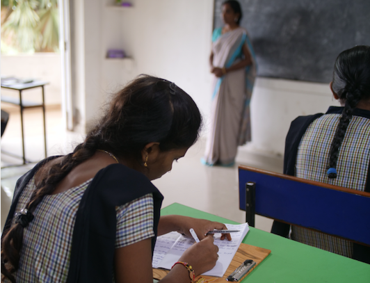 An Indian girl writes on a desk in classroom as she recovers from trafficking