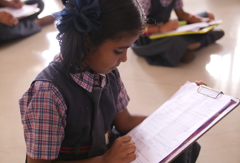 A young Indian girl does math on a clipboard provided by sponsorship