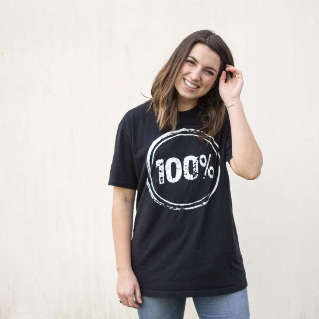 "Young woman wearing a black shirt with ""100%"" on the front to represent our commitment to being a 100% non-profit to fight human trafficking"