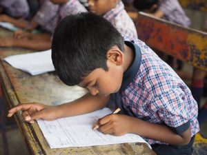 Little Indian boy rescued from human trafficking writes on a desk in a classroom