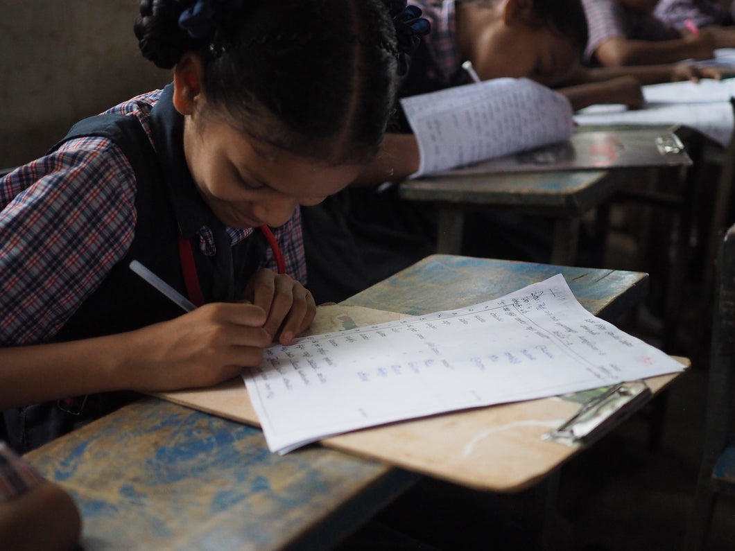 Little Indian girl rescued from human trafficking writes on a clipboard in a classroom