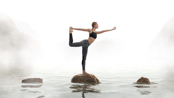 Lord-of-the-dance-Yoga-Pose-For-Energy-Vitality-Woman-Holding-Foot-On-Rock-In-Water