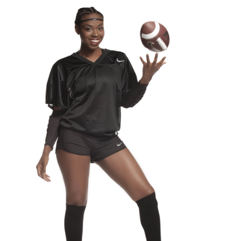 African American female tossing football wearing black jersey, black shorts and black socks