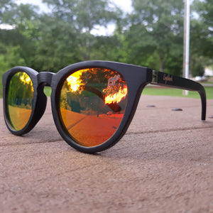 sunset mirror sunglasses with black wood arms outdoors