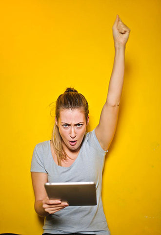 Girl Celebrating against a yellow background.
