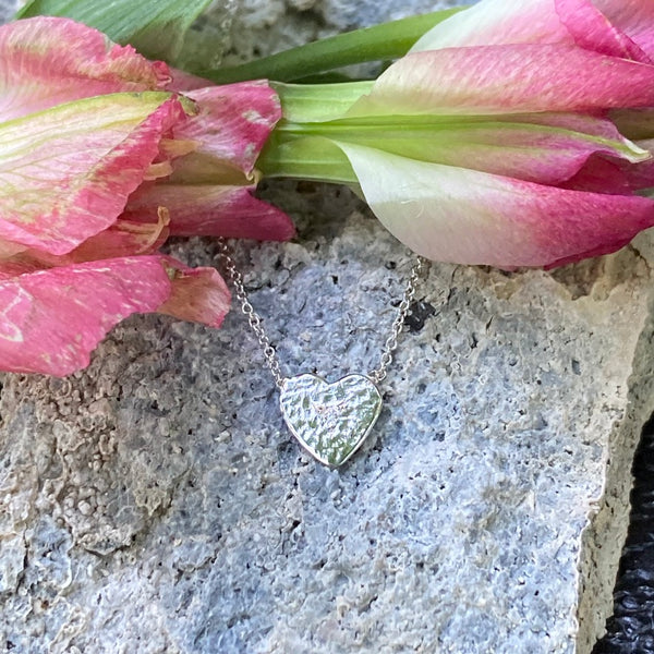 White gold necklace with heart shape on the bottom with a tiny white diamond. Background of stone and pink flowers.