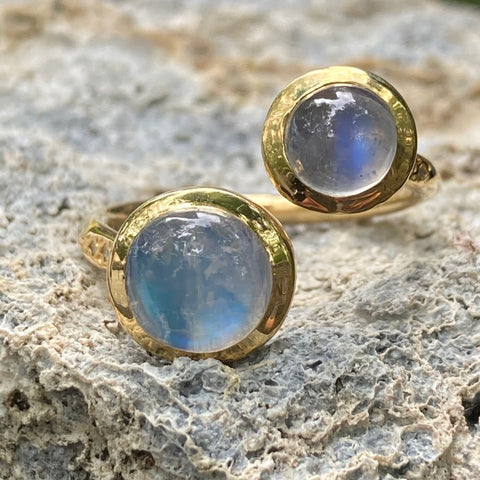 Gold ring with two large moonstones and diamonds along the side.