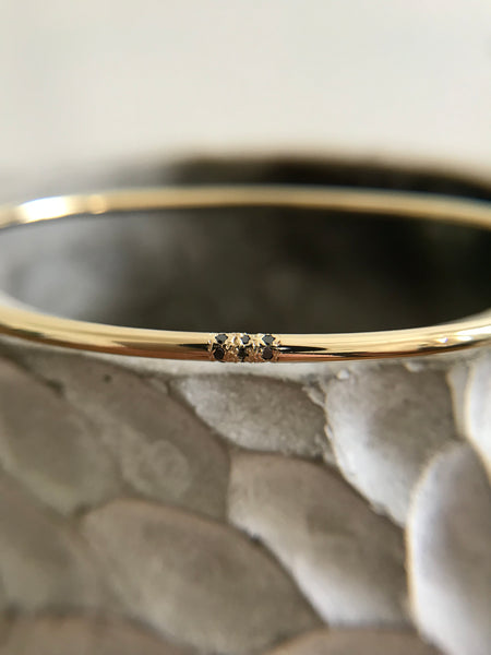Minimalistic Gold Cuff Bracelet with three small black diamonds
