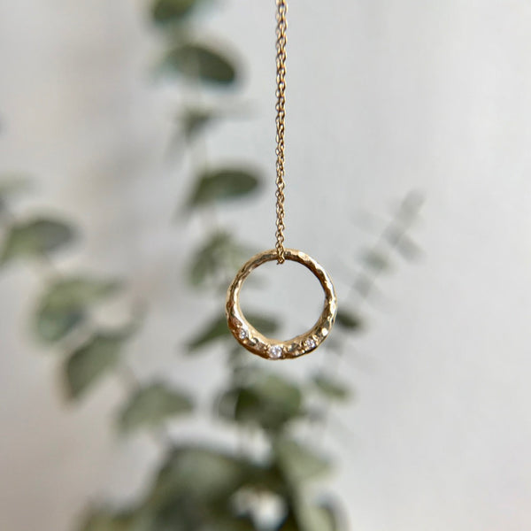 Crescent Moon full circle necklace with white diamonds in the forefront. Eucalyptus in the background.