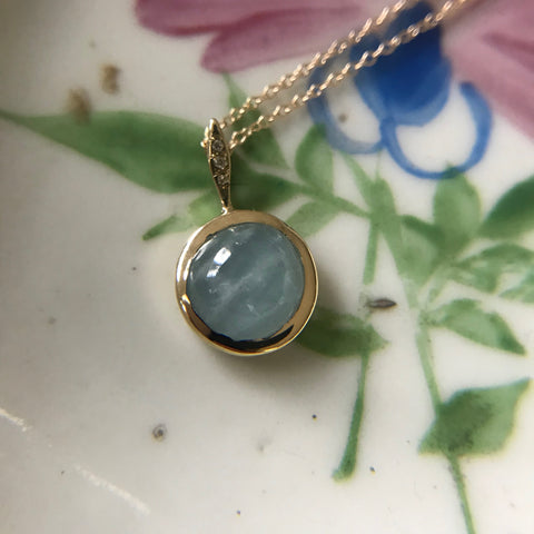 Gold pendant with large aquamarine or moonstone stone and three diamonds on the gold bail.