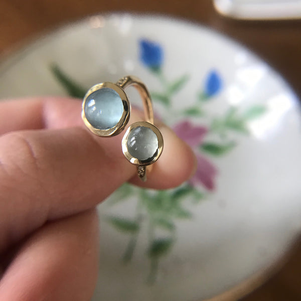 Three-quarter shot of gold ring with moonstone or aquamarine.