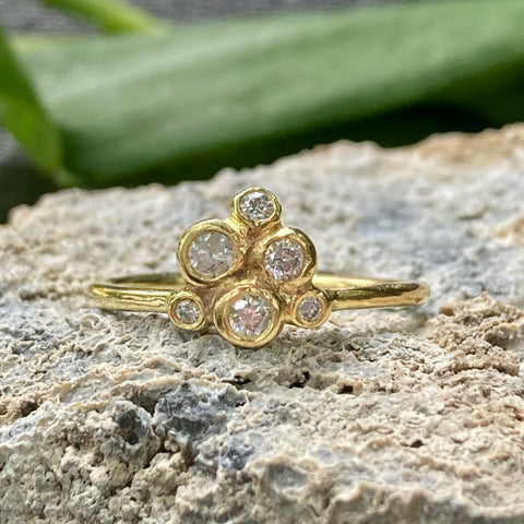 18k yellow gold ring with a cluster of varying sized diamonds.