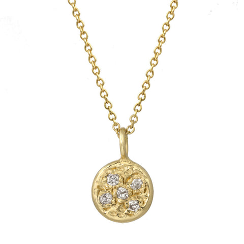 Circular pendant with bezeled pebble diamonds on a gold chain.