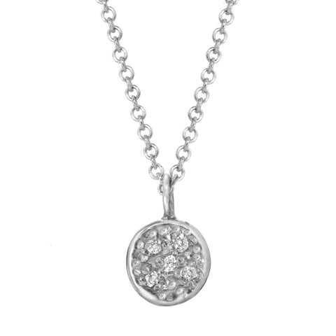 Circular pendant with bezeled pebble diamonds on a silver chain.