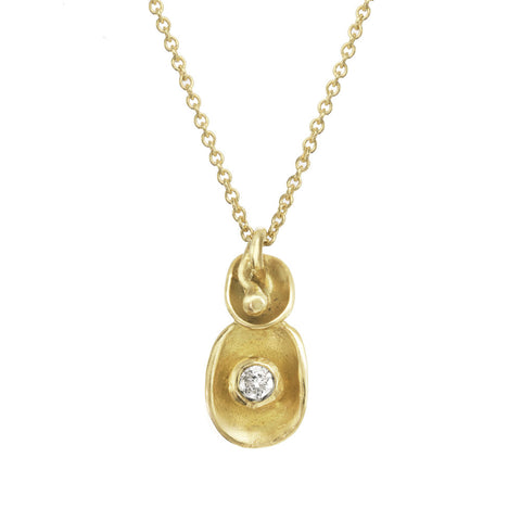 Waterlily inspired gold pendant with tiny diamond on a gold chain.