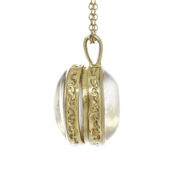 Gold locket with a Herkimer crystal on a gold chain side view.