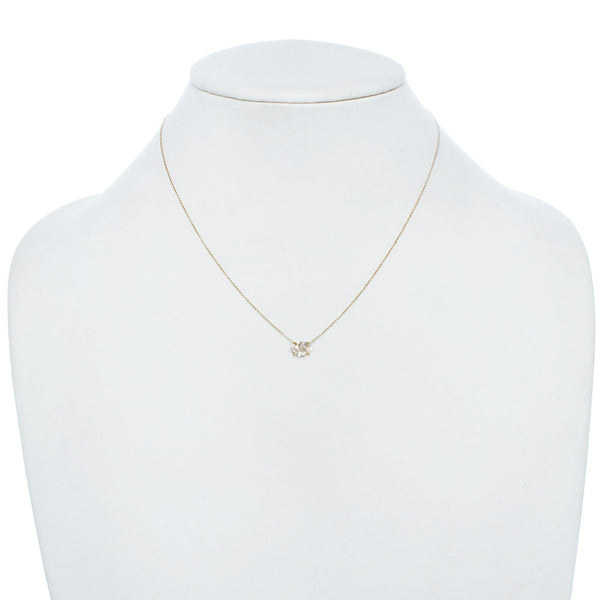 Delicate Herkimer Crystal pendant necklace with a gold chain on jewelry display.