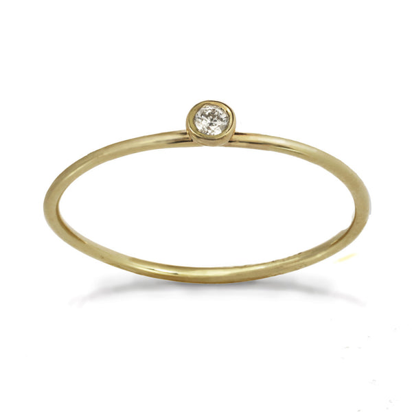 Delicate yellow gold ring with center white diamond stone.