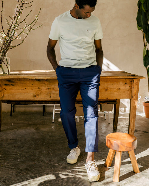 Man with navy chino pants leaning on a wooden table