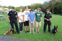 Police K-9 handlers posing with dogs and community members from North Huntingdon Township