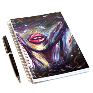 Abstract watercolor art piece of face focusing on the lips. Colors in this abstract piece are purple, pink, yellow, blue, and black. Very colorful but has a moody look. Black surrounds the face and frames it beautifully. This image shows a 5x7 spiral notebook with this abstract art piece on the cover. Art notebook is on a white background with pen next to it to show size. Artist is Erica Cantua. Her art is for sale on erixaart.com. Abstract art that encourages uniqueness and individuality.
