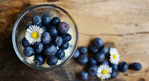 Blue berries in a bowl and on a table. A good source of vitamins and antioxidants